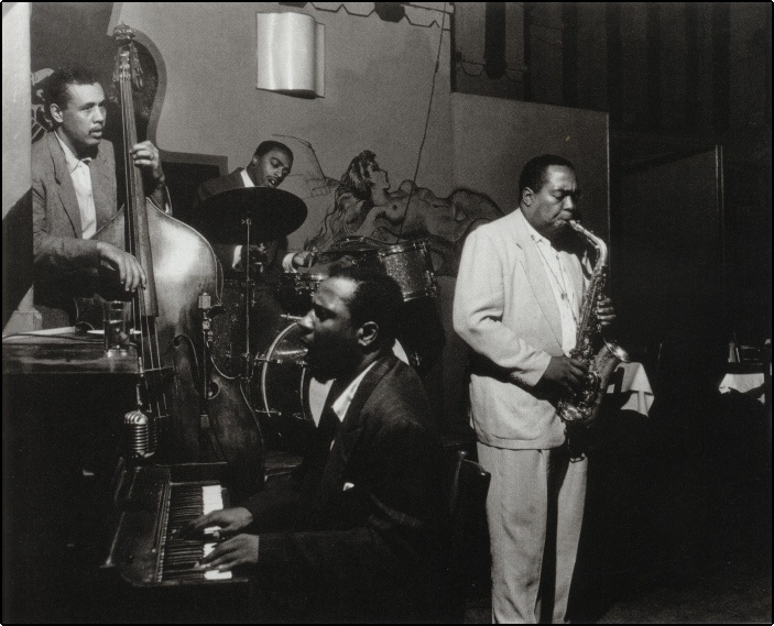 Charlie Parker (sax) Monk (piano) Mingus (bass) and Roach (drums) at a session