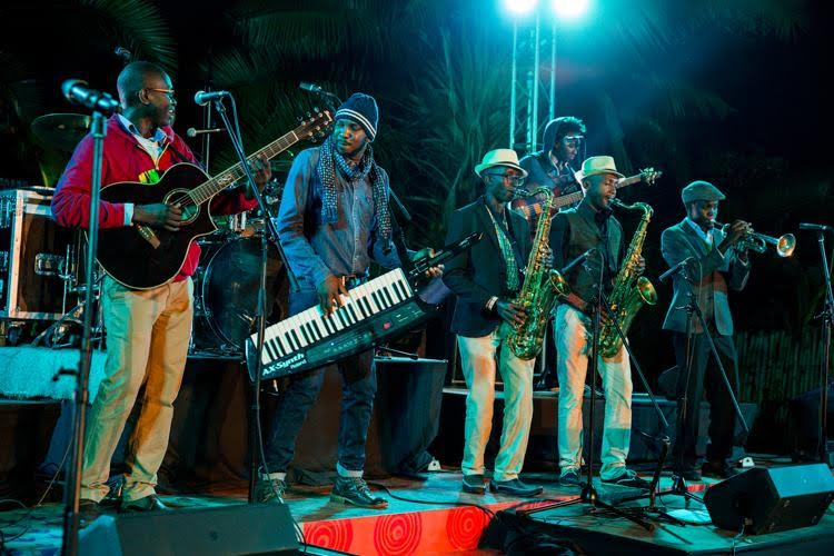 Tim Riungu performing alongside  Chris Adwar  Adorned with a fedora hat