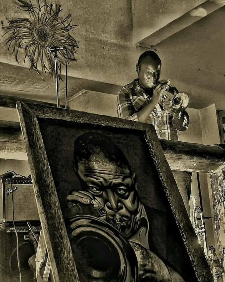 Mackinlay Mutsembi Playing his music next to a Hugh Masekela painting